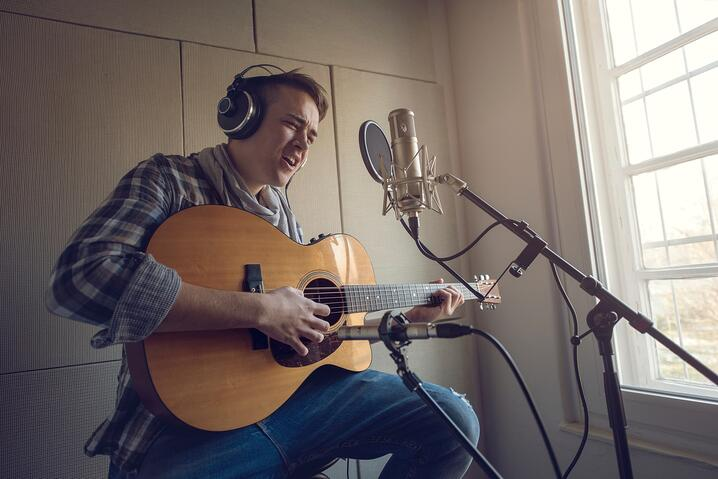 Young-man-playing-acoustic-guitar-and-singing-in-recording-studio-000087459773_Medium