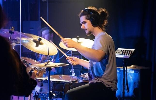 drummer-performing-at-a-music-college-near-white