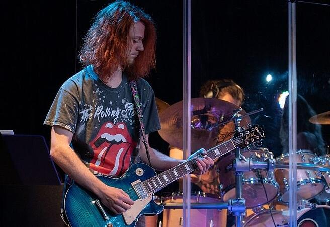 a-student-on-stage-during-a-guitar-degree-program