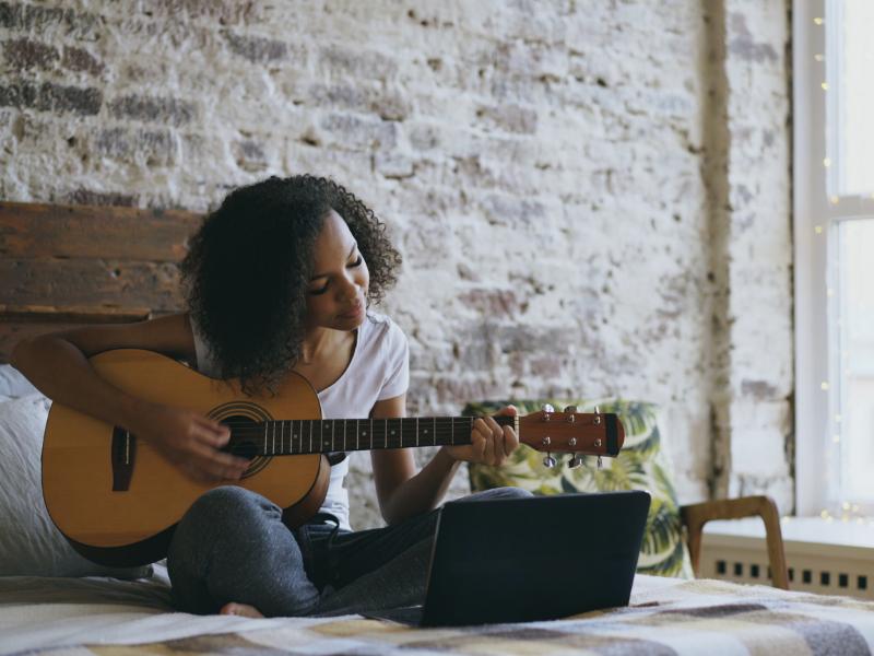 A woman taking an online guitar lesson